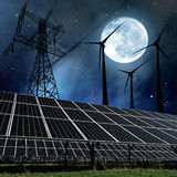 Solar panels with wind turbines and electricity pylon in night. Stock Image