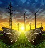 Solar panels with wind turbines and electricity pylon at sunset Stock Image
