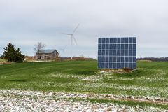 Solar Panels and Wind Turbines in a Field royalty free stock image