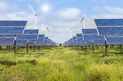 Solar panels and wind turbines generating electricity in power station green energy renewable. With blue sky background royalty free stock photos