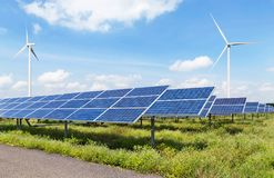 Solar panels and wind turbines in power station green energy renewable with blue sky background stock photography