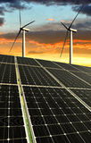 Solar panels with wind turbines. In the setting sun royalty free stock photography