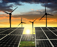 Solar panels with wind turbines. In the setting sun Royalty Free Stock Photo