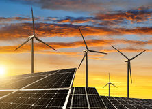 Solar panels with wind turbines. In the setting sun royalty free stock images