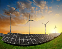Solar panels with wind turbines. In the setting sun Royalty Free Stock Image