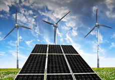 Solar panels with wind turbines in the setting sun. Royalty Free Stock Photography