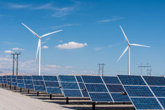 Solar panels and wind turbines in sunny desert Royalty Free Stock Images