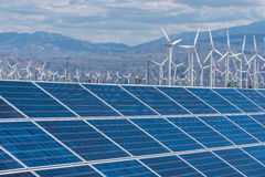 Solar panels and wind turbines in sunny desert Stock Photography