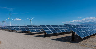 Solar panels and wind turbines in sunny desert Stock Images