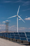 Solar panels and wind turbines in sunny desert Stock Photos