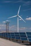 Solar panels and wind turbines in sunny desert Stock Photos