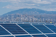 Solar panels and wind turbines in sunny desert Stock Image