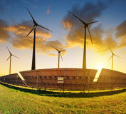 Solar panels with wind turbines at sunset. Royalty Free Stock Photography