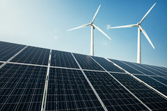 Solar panels and a windmill generate electricity from the sun. Renewable sources of energy royalty free stock photography