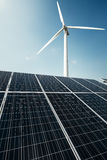 Solar panels and a windmill generate electricity from the sun. Renewable sources of energy stock image