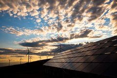 Solar panels and windmills at sunset. Solar panels and wind turbines at sunset stock photo