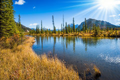 Solar patches of light. Magic lakes Vermillon in the Rocky Mountains of Canada. Concept of active tourism and ecotourism. Solar patches of light in smooth water Royalty Free Stock Images