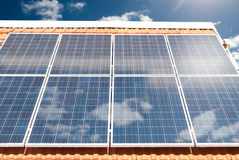 Solar (photovoltaic) panels on a house roof. Solar (photovoltaic) panels producing electricity on a house roof during a sunny day Stock Images