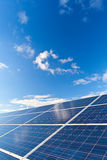 Solar photovoltaics panels. Field for renewable energy production with blue sky and clouds Royalty Free Stock Photos