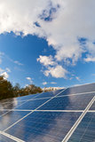 Solar photovoltaics panels. Field for renewable energy production with blue sky and clouds Royalty Free Stock Images