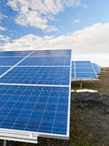 Solar photovoltaics panels. Field for renewable energy production with blue sky and clouds Stock Images