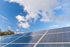 Solar photovoltaics panels. Field for renewable energy production with blue sky and clouds Stock Photos