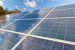 Solar photovoltaics panels. Field for renewable energy production with blue sky and clouds Stock Photography