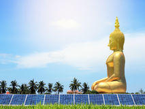 Solar photovoltaics panels in rice field with big buddha statue sitting background. Royalty Free Stock Photos