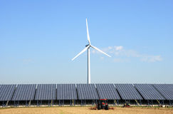 Solar plant with wind turbine at a farm Royalty Free Stock Photo