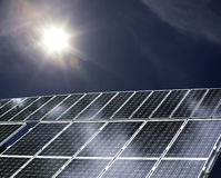 Solar power. Detail of a solar power plant with sun shining on it Royalty Free Stock Photos
