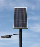 Solar Power Light. Outdoor light powered with a single solar panel set against a blue sky.  The latest technology available for renewable energy Stock Photos