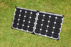 Solar Power Panels. Portable solar panels on green grass. Solar power has become a mainstay of the glamping camping recreation Stock Photography