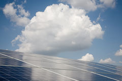 Solar power plant. Line of solar power plant panels and clouds Royalty Free Stock Photography