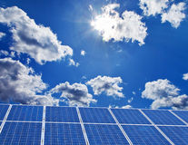 Solar power plant for solar energy. Solar panels against a blue sky with clouds Stock Image