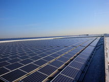 Solar power rooftop. Endless rows of solar panels on a big roof Royalty Free Stock Images