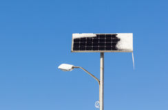Solar power street light with snow and ice on blue sky background Stock Image