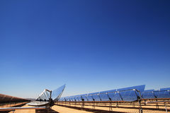 Solar power thermal mirrors. Side view of SEGS solar thermal energy desert electricity plant with parabolic mirrors concentrating the sunlight with blue sky copy stock photos