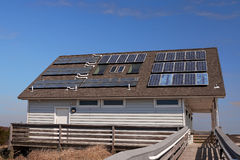 Solar-Powered Building at the Shore. A building at the seashore uses solar water heating and electricity for its energy needs Stock Photo