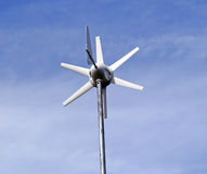 Solar powered environment friendly wind turbine. Over a blue sky background Royalty Free Stock Images