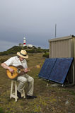 Solar powered guitarist with lighthouse Royalty Free Stock Image