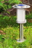 Solar-powered lamp on garden background. Stock Photo