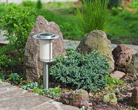 Solar-powered lamp on garden background. Royalty Free Stock Photos