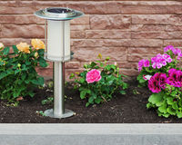 Solar-powered lamp on garden background. Royalty Free Stock Photo