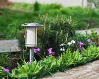 Solar-powered lamp on garden background. Royalty Free Stock Images