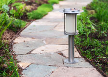 Solar-powered lamp on garden path. Royalty Free Stock Image