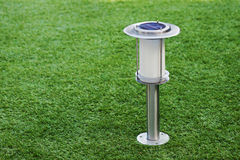 Solar-powered lamp on green grass background. Stock Photos