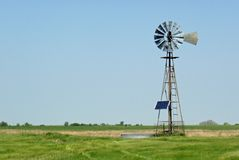 Solar Powered Windmill on the Ranch. A windmill equipped with a solar power screen on a rural ranch Royalty Free Stock Image