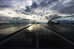 Solar-PV-Dachspitze mit Sonnenaufgang-bewölktem Himmel lizenzfreie stockfotografie