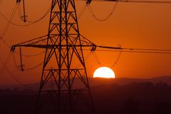 Solar pylon. Sun setting behind a silhouetted electricity pylons stock photos