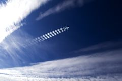 Solar sky and turbojet plane. Jet plane and contrail high in the sky royalty free stock photo